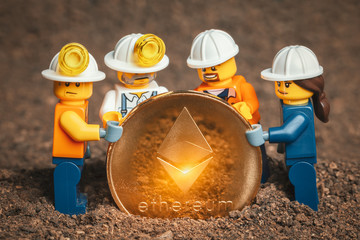 ANKARA, TURKEY. NOVEMBER 17, 2019. Group of Lego mini miner figurines holding shiny ethereum together and posing.  Cryptocurrency, blockchain and mining concept.