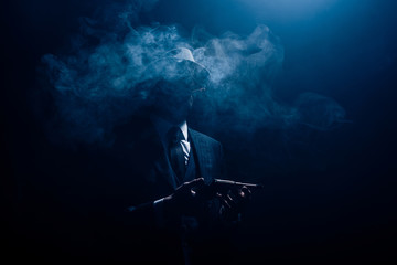 Silhouette of gangster holding gun and smoking on dark background Wall mural