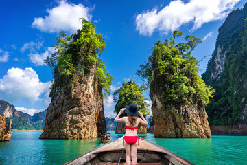 Wall Mural - Beautiful girl standing on the boat and looking to mountains in Ratchaprapha Dam at Khao Sok National Park, Surat Thani Province, Thailand.