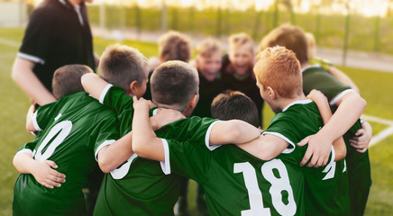 Coaching Youth Sports. Group Of Children In Soccer Team. School Football Coach's Pregame Speech. Young Boys United In Football Team