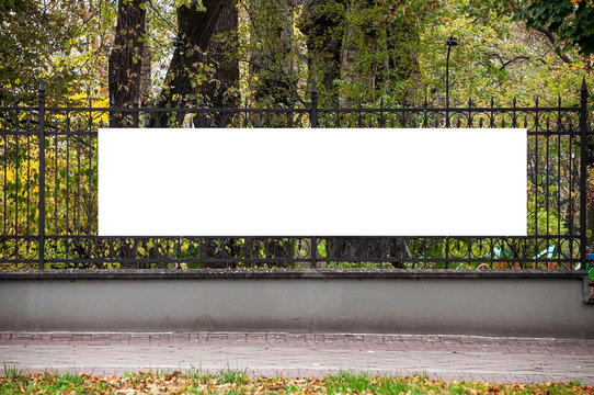 Blank white banner for advertisement on the fence of the park in the city