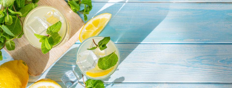 Lemonade and ingredients on blue wood background, copy space