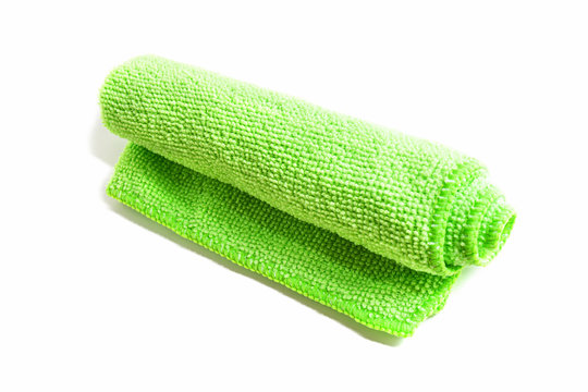 Green microfiber cloth on a white background. Cleaning cloth, napkin. Folded towel for cleaning objects and surfaces.