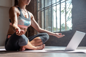 Fotobehang School de yoga Closeup young sporty fit slim woman coach do practice video online training hatha yoga instructor modern laptop meditate Sukhasana posture relax breathe easy seat pose gym healthy lifestyle concept.