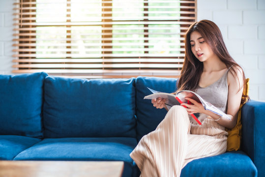 Young beautiful Asian woman sitting on blue sofa and reading magazine at living room in the morning