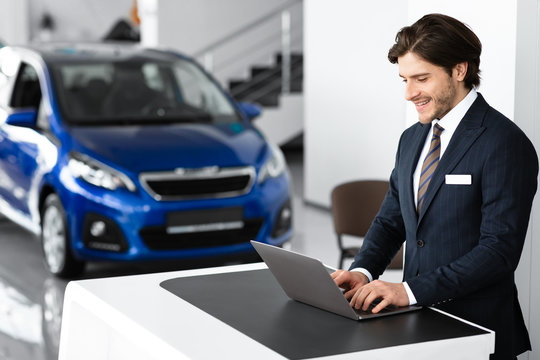 Young Car Seller Standing In Luxury Dealership Office