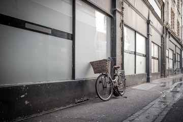 Photo sur Toile Velo Old fashioned bicycle with a wicker basket seen leaned up against a glass window for an old building in an empty city side street.