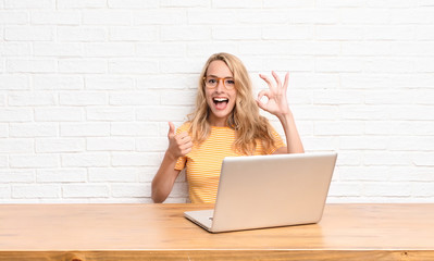 young blonde woman feeling happy, amazed, satisfied and surprised, showing okay and thumbs up gestures, smiling using a laptop Wall mural