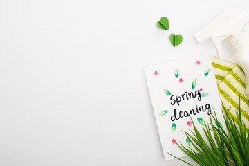 top view of green grass and cleaning supplies near spring cleaning card on white background