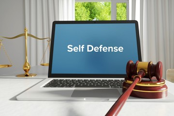 Self Defense – Law, Judgment, Web. Laptop in the office with term on the screen. Hammer, Libra, Lawyer.