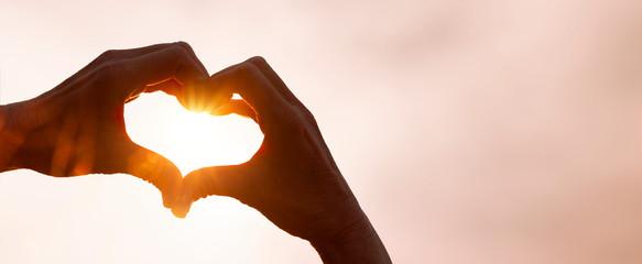 Als Herz geformte Hand im Gegenlicht