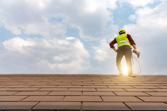 Construction workers lay a roof with a nail gun to develop a large commercial building.