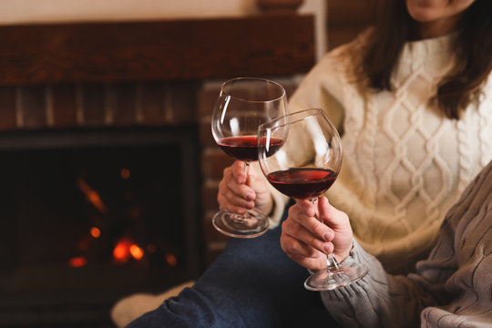 Lovely couple with glasses of wine resting near fireplace at home, closeup. Winter vacation