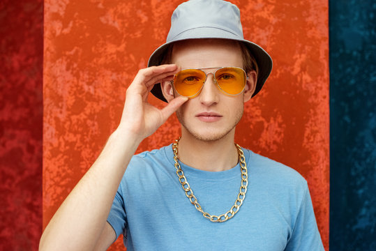 Close up portrait of young fashionable confident handsome man wearing orange color sunglasses, blue bucket hat, t-shirt, golden chain, posing against colorful background. Copy, empty space for text