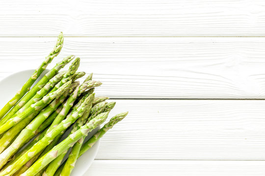 Fresh asparagus on plate on white wooden background top-down copy space