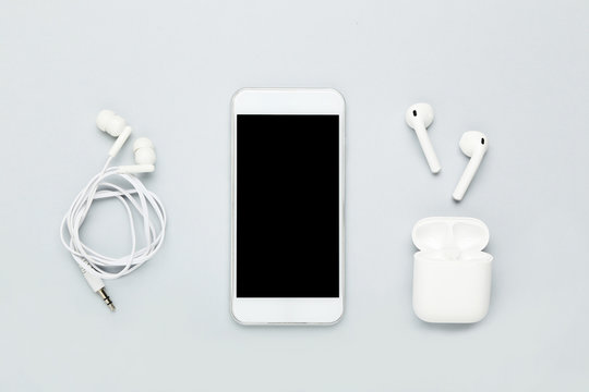White wireless earbuds with earphones and mobile phone on grey background