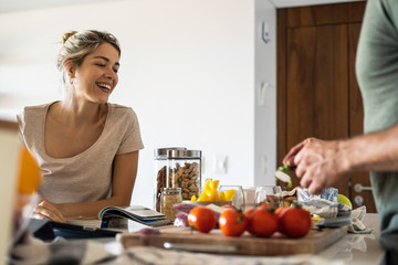 Happy young man preparing food in kitchen