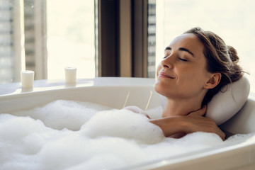Close-up of young woman relaxing while taking a bath in bathtub