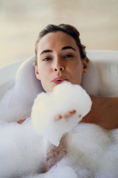 Portrait of young woman blowing foam while taking bubble bath in bathroom