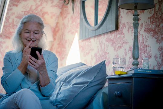 Happy senior woman looking at smart phone while sitting on bed in bedroom at home