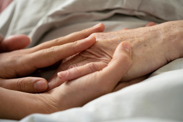 Close-up of home carer consoling senior female patient at nursing home