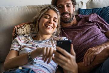 Smiling couple using smartphone while relaxing on sofa at home