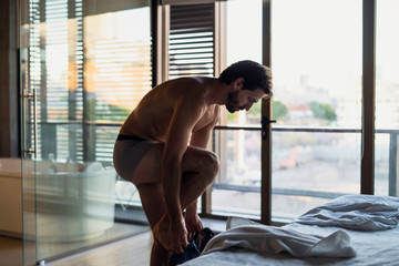 Side view of young man getting dressed at home