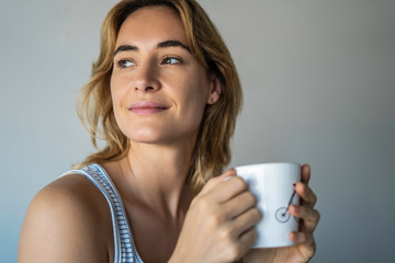 Thoughtful young woman holding coffee mug against white background