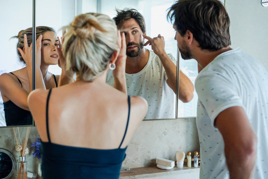Young couple looking their face in mirror in the bedroom