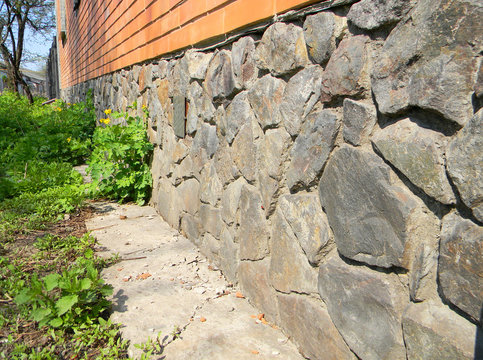 Brick house foundation wall from wild stone for waterproofing protection