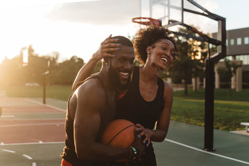 An Attractive African American Couple playing basketball on a sunny day