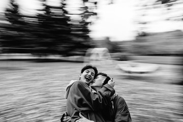 Young couple hug and kiss On The Merry-Go-Round