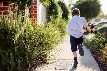 Boy in a school uniform running along a path after school