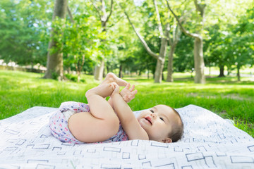 Playful Interracial baby, playing with hands and feet in park