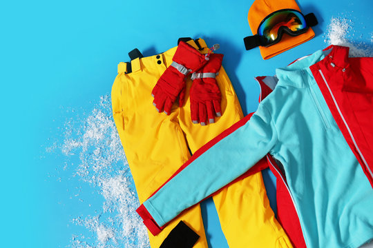 Stylish winter sport clothes on light blue background, flat lay