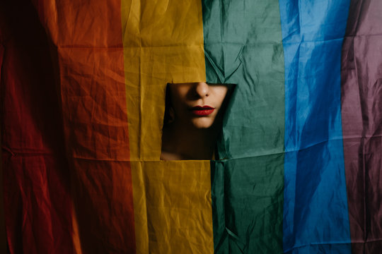 Close up of woman's face seen through window in rainbow flag