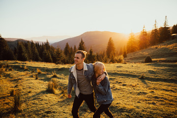 Man and woman walking on the mountain at sunset. Loving couple embracing and walking at sunset in the meadow mountain in background. Valentine's Day and love concept. Wall mural