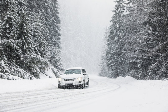 Modern car on snowy road near forest. Winter vacation