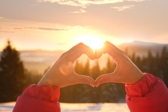 Woman making heart with hands outdoors at sunset, closeup. Winter vacation