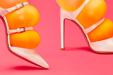Close up of orange inflated balloons in stilettos Wall mural