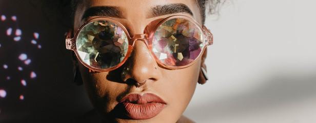 A woman in her twenties wearing prismatic glasses