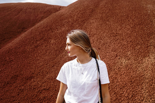 Woman looking left with scenic red hills in the background