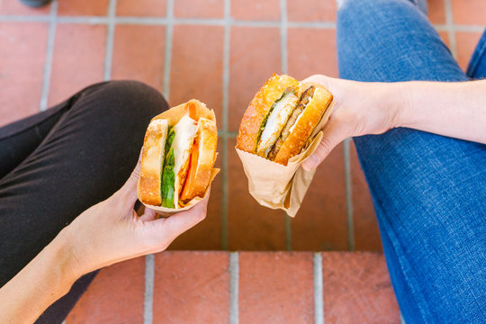 Two female hands holding out sandwiches to show ingredients in middle including egg, avocado, sausage, and tomato.