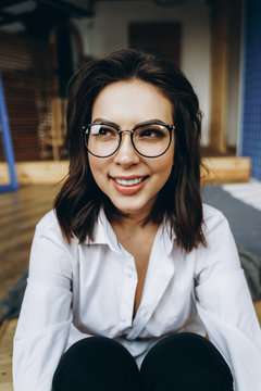 Vertical portrait of happy smiling woman wearing eyeglasses and looking aside