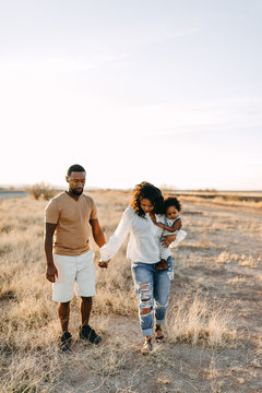 An African American husband & wife and their child walking outdoors.