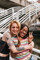 two girl friends in a embrace, one with tattooed arms hugging a brunette woman doing peace sing.