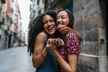 curly hair woman and ans asian woman hugging and laughing each o