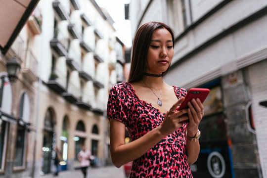 Asian woman wearing a red printed dress and a choker necklace, is holding a phone searching for directions