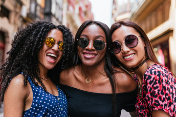Brown skinned women wearing sunglasses and laughing together.