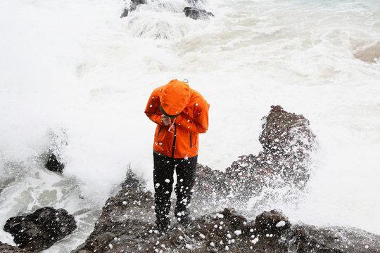 man in waterproof coat standing on rocks at beach splashed by waves